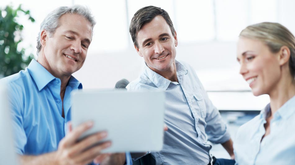 businessman using a tablet to show new website to his colleagues